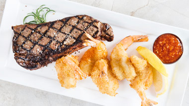 New York Strip Steak with fried shrimp, lemon and cocktail sauce
